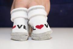 Manos que sostienen pequeños calcetines del bebé fotos de archivo
