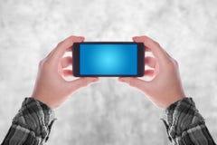 Manos que sostienen smartphone Imágenes de archivo libres de regalías