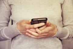 Manos que sostienen smartphone entonado en estilo del vintage Foto de archivo libre de regalías