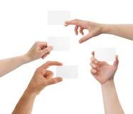 Manos que sostienen tarjetas de visita en blanco con el copia-espacio Fotos de archivo
