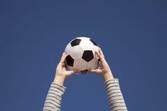 Manos que sostienen un balón de fútbol Imagen de archivo