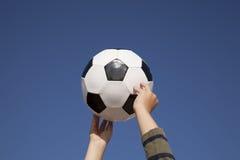 Manos que sostienen un balón de fútbol Imagen de archivo libre de regalías