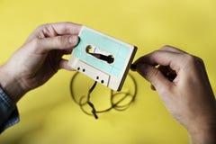 Manos que sostienen un casete de cinta que rueda detrás Imagenes de archivo