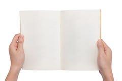 Manos que sostienen un libro en blanco Foto de archivo libre de regalías