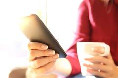 Manos que sostienen un teléfono móvil y una taza de café Imagenes de archivo