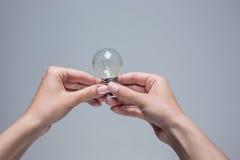 Manos que sostienen una bombilla incandescente en fondo gris fotos de archivo libres de regalías