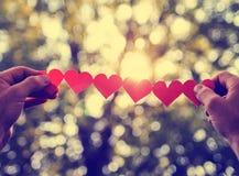 Manos que sostienen una cadena de corazones de papel hasta el sol durante los soles Imagen de archivo libre de regalías