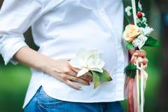 Manos que sostienen una flor en el vientre de una mujer embarazada Foto de archivo