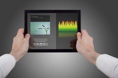 Manos que sostienen una PC del touchpad, usando programa de la música Fotos de archivo