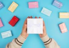 Manos que sostienen una pequeña caja con un regalo foto de archivo libre de regalías