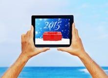 Manos que sostienen una tableta con el saludo de la Navidad Imagen de archivo libre de regalías