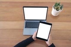Manos que sostienen una tableta y un ordenador portátil negros con la pantalla blanca en blanco en la tabla de madera en oficina imagenes de archivo
