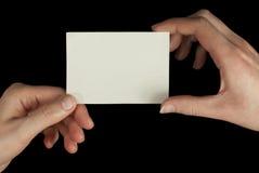 Manos que sostienen una tarjeta blanca Imagen de archivo libre de regalías