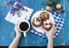 Manos que sostienen una taza azul Desayuno con las galletas y las bayas frescas Fotografía de archivo libre de regalías