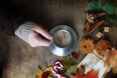 Manos que sostienen una taza de café caliente en una tabla Imagen de archivo libre de regalías