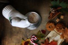 Manos que sostienen una taza de café caliente en una tabla Fotografía de archivo libre de regalías