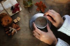 Manos que sostienen una taza de café caliente en una tabla Imagen de archivo