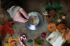 Manos que sostienen una taza de café caliente en una tabla Foto de archivo libre de regalías