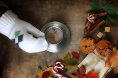 Manos que sostienen una taza de café caliente en una tabla Imágenes de archivo libres de regalías