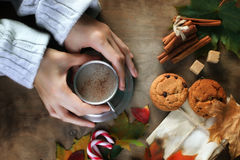 Manos que sostienen una taza de café caliente en una tabla Fotografía de archivo