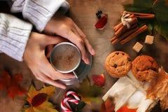 Manos que sostienen una taza de café caliente en una tabla Fotos de archivo