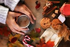Manos que sostienen una taza de café caliente en una tabla Fotos de archivo libres de regalías