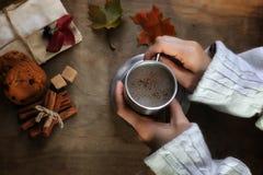 Manos que sostienen una taza de café caliente en una tabla Imagenes de archivo