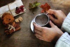 Manos que sostienen una taza de café caliente en una tabla Foto de archivo