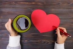 Manos que sostienen una taza de café y que escriben a la tarjeta del día de San Valentín decoraciones del día de tarjetas del día Imagenes de archivo