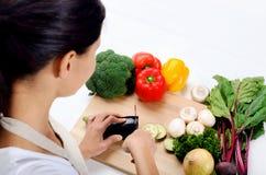 Manos que sostienen verduras del corte del cuchillo Foto de archivo libre de regalías