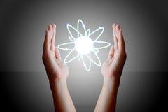 Manos que sostienen y que ahuecan un átomo que brilla intensamente Fotos de archivo libres de regalías
