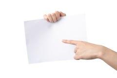 Manos que sostienen y que señalan A4 de papel, aislado en blanco Foto de archivo libre de regalías