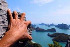 Manos que suben la roca en la isla de Angthong del punto de vista Imagenes de archivo