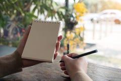 Manos que sujetan y que escriben hacia abajo en un cuaderno en blanco con el fondo de la naturaleza de la falta de definición Fotos de archivo libres de regalías