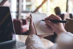 Manos que sujetan y que escriben hacia abajo en un cuaderno en blanco con el ordenador portátil del ordenador en la tabla Imágenes de archivo libres de regalías