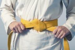 Manos que tensan la correa amarilla en un adolescente vestida en kimono Imágenes de archivo libres de regalías