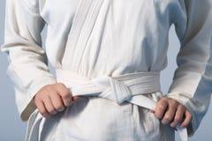 Manos que tensan la correa blanca en un adolescente vestida en kimono Fotos de archivo