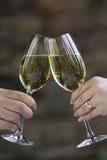 Manos que tintinean dos vidrios de vino blanco. Imagenes de archivo