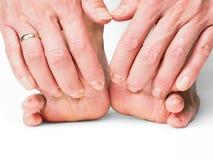 Manos que tiran de los dedos del pie en pies descalzos Imagenes de archivo