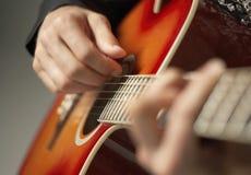 Manos que tocan la guitarra imagen de archivo