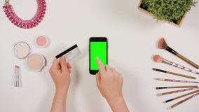 Manos que tocan Smartphone y que sostienen la tarjeta de crédito metrajes