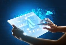 Manos que tocan una tableta transparente con los gráficos azules imagen de archivo