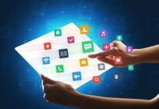 Manos que tocan una tableta transparente con los iconos coloridos Imágenes de archivo libres de regalías