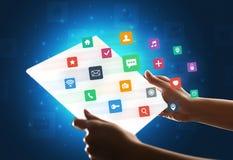 Manos que tocan una tableta transparente con los iconos coloridos Imagen de archivo