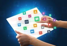 Manos que tocan una tableta transparente con los iconos coloridos Imagen de archivo libre de regalías