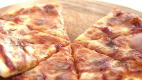 Manos que toman cortes de la pizza de la tabla de madera almacen de metraje de vídeo