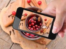 Manos que toman el vino reflexionado sobre foto con smartphone Imagen de archivo libre de regalías
