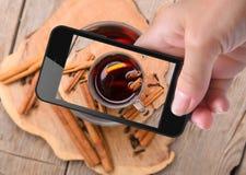 Manos que toman el vino reflexionado sobre foto con smartphone Fotos de archivo