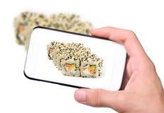 Manos que toman a foto los rollos de sushi japoneses frescos con smartphone Foto de archivo libre de regalías