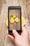 Manos que toman la foto de frutas en de madera imagenes de archivo